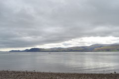 Lake with Moody Sky. Pebble beach with dull water across which are low mountains, thin slither of pale sky can be seen under the dark grey clouds, has a moody Royalty Free Stock Photography