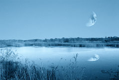Lake with moon in the sky Stock Images