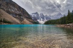 Lake Moraine, Alberta, framed by trees Stock Images
