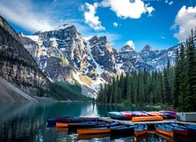 BEAUTIFUL LAKE MORAINE WITH SEVERAL CANOES WITH MOUNTAIN BACKGROUND Stock Photography