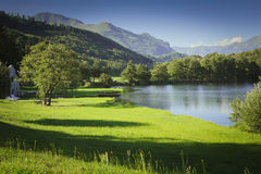 Lake in mountain with green field and blue sky Royalty Free Stock Photography