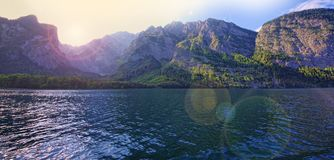 Lake and mountain landscape with lens flare. Effect added from sun stock photography