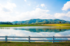 The lake and mountain with white hedge fence on blue sky backgro. Lake and mountain with white hedge fence on blue sky background Royalty Free Stock Photo