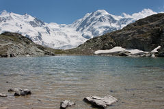 Lake in the mountains. A small lake with snow covered mountains in the back ground. Switzerland: Monta Rosa Group Royalty Free Stock Photography