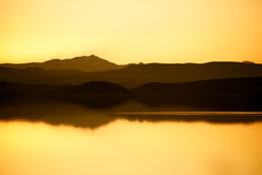 Lake with mountains. Quiet lake with mountains in the background before sunset with yellow sky and reflection in the water. Copy space. Concept of stillness and Stock Image