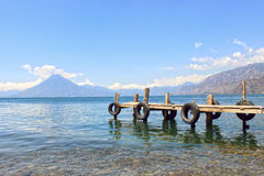Lake and mountains. Wooden jetty with tyres on lake against blue sky Stock Photography