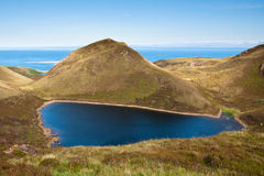 Lake in the Mountains. Blue lake in the mountains called Quiraing on the Isle of Skye overlooking the sea Stock Photography