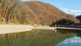 Lake in the mountains and autumn forest. Lake in the mountains of Krasnaya Polyana, mountain resort Rosa Khutor, autumn forest and blue sky Royalty Free Stock Images