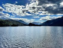 Lake with Mountains in the Background on Blue Sky Day. Blue skies filled with clouds create a dramatic scene over an open lake with mountains in the distance royalty free stock photography