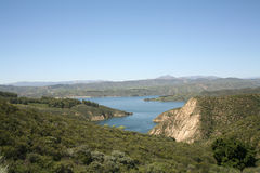 A lake in the mountains. A blue mountain lake in a green arid forest with some exposed rock face and mountains in the background Stock Photo