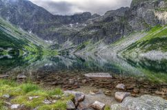 Lake in mountains. Clear and symmetrical mirror reflection of mountains and clouds royalty free stock images