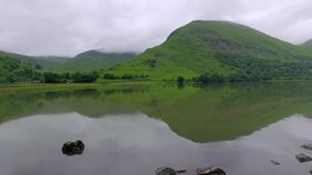 Lake and mountains on a cloudy day in the Lake District, England. Lake and mountains on a cloudy day in the Lake District in England stock video footage