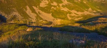The lake in mountains a decline. The mountains lit with the sunset sun are reflected in the mountain lake Stock Images