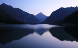 Lake with mountains at evening Stock Images