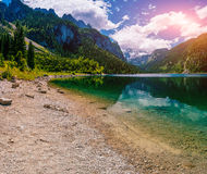 Lake between mountains. Fantastic cumulus white clouds in blue sky. Italy Royalty Free Stock Photography