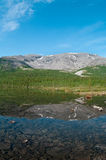 Lake in mountains and forest around it. Royalty Free Stock Images