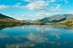 Lake in mountains and forest around it. Stock Photos