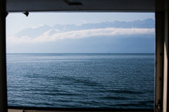 Lake and Mountains. French Alps with the Lake Geneva in the foreground photographed from a ship that frames the photo Stock Photo
