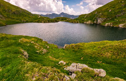 Lake in mountains with grass on hillside. Clear lake in mountains with grass on rocky hillside. beautiful mountain ridge in far distance. dramatic weather in royalty free stock image