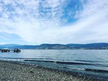 Lake shore and beach with boat on dock. Lake and mountains landscape view with covered boat on dock. Waves rolling on rocky beach. White clouds and blue sky over Stock Photography