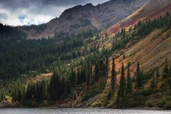 Lake in the Mountains. Mountain Lake with evergreens flanking the steep banks. Foliage in autumn color. Sunlight highlighting various colorful ground cover Royalty Free Stock Photo