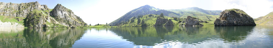 The lake in mountains, panorama 180. This is mountain lake in a sunny weather in high mountains royalty free stock images