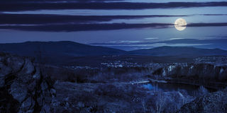 Lake in mountains quarry near city at night. Collage of small lake in an abandoned stone quarry in the mountains outside the city at night in full moon light Royalty Free Stock Images