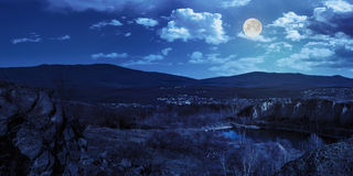 Lake in mountains quarry near city at night. Collage of small lake in an abandoned stone quarry in the mountains outside the city at night in full moon light Stock Photo