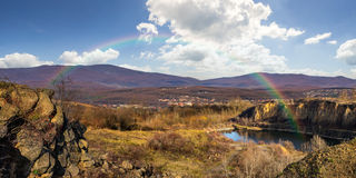 Lake in mountains quarry near city with rainbow. Collage of small lake in an abandoned stone quarry in the mountains outside the city with rainbow in morning Stock Image