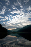 Lake in the mountains in reflection of the dawn sky Stock Photos
