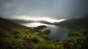 Lake in the mountains, Sete Citades - Azores, Sao Miguel Island. Volcano lake in between the mountains partly covered with clouds during the morning royalty free stock photography