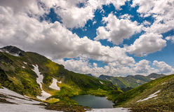 Lake in mountains with snow on hillside. Clear lake in mountains with snow and grass on rocky hillside. dramatic weather in picturesque summer scenery stock image