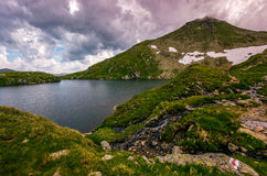 Lake in mountains with snow on hillside. Clear lake in mountains with snow and grass on rocky hillside. dramatic weather in picturesque summer scenery royalty free stock image