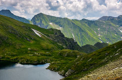 Lake in mountains with snow on hillside. Clear lake in mountains with snow and grass on rocky hillside. fine weather in picturesque summer scenery Royalty Free Stock Photography
