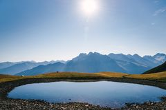 Lake in the mountains and the sun royalty free stock photography