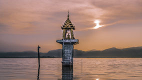 Lake and mountains at sunset with a buddhist altar in the middle. Altar in the middle of a lake surrounded by mountains at sunset in Myanmar, very calm and Stock Photo