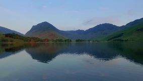 Lake and mountains at sunset in calm day in the Lake District, England stock footage