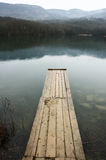 Lake and mountains. Lake with wooden pier and mountains in background at rainy day. Bad weather, rain falls royalty free stock photography