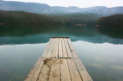 Lake and mountains. Lake with wooden pier and mountains in background at rainy day. Bad weather, rain falls stock image