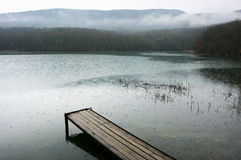 Lake and mountains. Lake with wooden pier and mountains in background at rainy day. Bad weather, rain falls stock photo