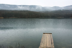 Lake and mountains. Lake with wooden pier and mountains in background at rainy day. Bad weather, rain falls stock images