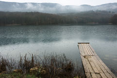Lake and mountains. Lake with wooden pier and mountains in background at rainy day. Bad weather, rain falls stock photography