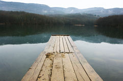 Lake and mountains. Lake with wooden pier and mountains in background at rainy day. Bad weather, rain falls royalty free stock photo