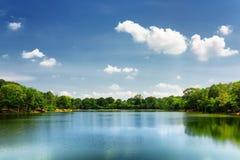 Lake nestled among rainforest in Cambodia under blue sky Stock Photo
