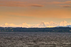 Lake Neuchatel and Alps. Scenic view of lake Neuchatel with snow capped Alps mountains in background, Switzerland Stock Image