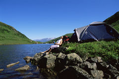 lake next relaxing rocks to woman young Στοκ εικόνες με δικαίωμα ελεύθερης χρήσης