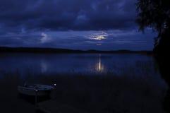 Lake at night. A small boat in a lake at night Stock Photos