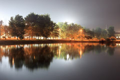 Lake night trees reflactions streetlight Stock Photos