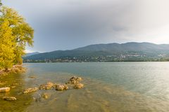 Lake in northern Italy, sunlight after the rain. Lake Varese, in the background the town of Gavirate. Lake Varese at dawn. The low sun, between the clouds royalty free stock image