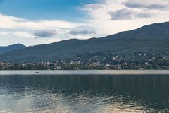 Lake in northern Italy. Lake Varese and the small town of Gavirate. Lake Varese on a summer morning, in the background the lakeside promenade of Gavirate and the Stock Photography